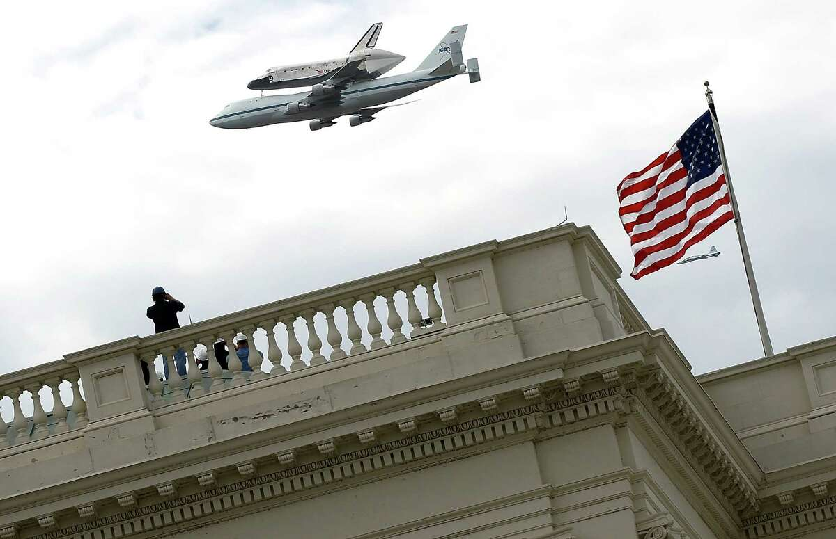 WASHINGTON, DC - APRIL 17: Space Shuttle Discovery, mounted atop a 747 shuttle carrier aircraft, flies over the U.S. Capitol during a flyover of the nation's capital on its final trip to its retirement place April 17, 2012 in Washington, DC. The longest-serving orbiter in the space shuttle fleet was flown from Kennedy Space Center in Florida to the Washington, DC area to be transferred to the Smithsonian National Air and Space Museum and will be placed on display in the museum's Steven F. Udvar-Hazy Center.