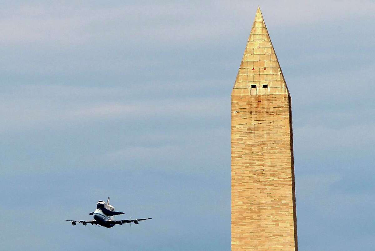 WASHINGTON, DC - APRIL 17: Space shuttle Discovery mounted atop a 747 shuttle carrier aircraft, flies by the Washington Monument during a flyover of the nation's capital on its final trip to its retirement place April 17, 2012 in Washington, DC. The longest-serving orbiter in the space shuttle fleet was flown from Kennedy Space Center in Florida to the Washington, DC area to be transferred to the Smithsonian National Air and Space Museum and will be placed on display in the museum's Steven F. Udvar-Hazy Center.