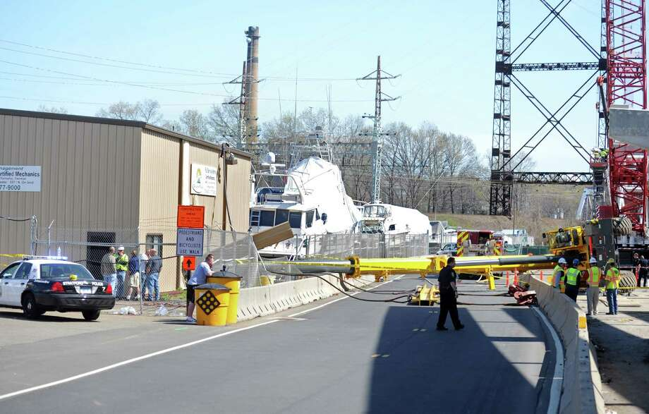 A crane lays across an access road in The Dock Shopping Center off Main Street in Stratford.  Police said the crane's boom toppled onto a metal building and struck an electrical panel near a work staging area for the Moses Wheeler Bridge construction project Saturday, April 14, 2012. Photo: Autumn Driscoll / Connecticut Post