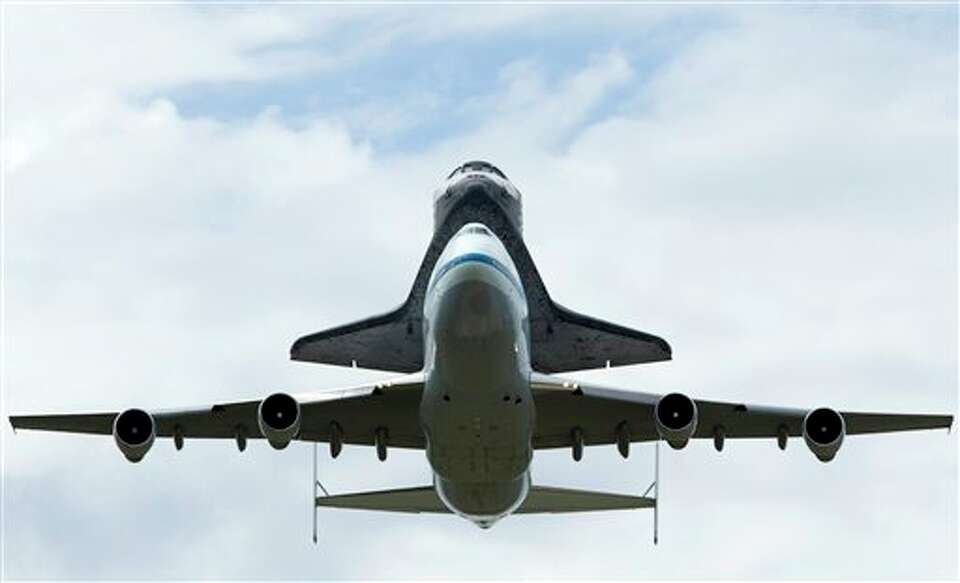 The space shuttle Discovery, sitting atop a 747 carrier aircraft lands, at Dulles International Airp