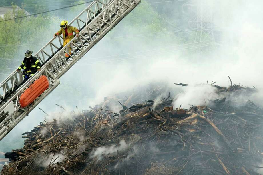 Firefighters battle a huge mulch fire at Shamrock Organic Products in Knoxville, Tenn., in this April 16, 2012 photo. Dozens of firefighters directed streams of water onto piles of mulch burning near downtown Knoxville for a third day Tuesday, April 17, 2012. The local health department issued a warning that the smoke was unhealthful for anyone in the immediate vicinity.  (AP Photo/Knoxville News Sentinel, Saul Young) Photo: Saul Young, Associated Press / The Knoxville News Sentinel