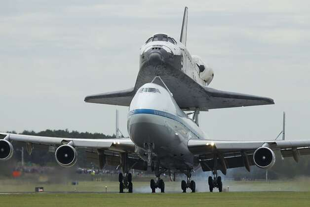 The space shuttle Discovery, sitting atop a 747 carrier aircraft, lands at Dulles International Airport in Chantilly, Va., Tuesday, April 17, 2012. Discovery, the longest-serving orbiter will be placed to its new home, the Smithsonian's National Air and Space Museum's Steven F. Udvar-Hazy Center in Chantilly, Va.    (AP Photo/Manuel Balce Ceneta) Photo: Manuel Balce Ceneta, Associated Press