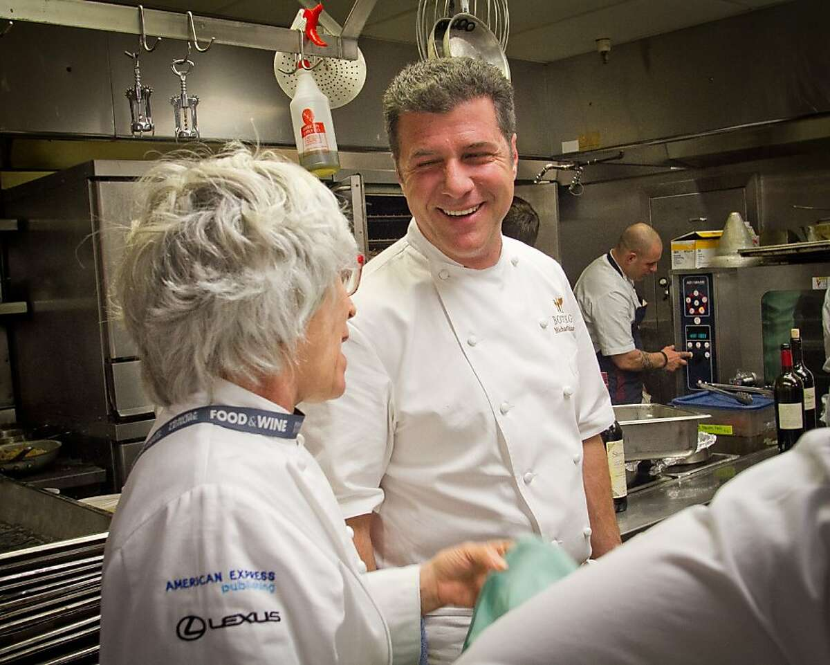 Chef Michael Chiarello talks with chef Cindy Pawlcyn in the kitchen during the