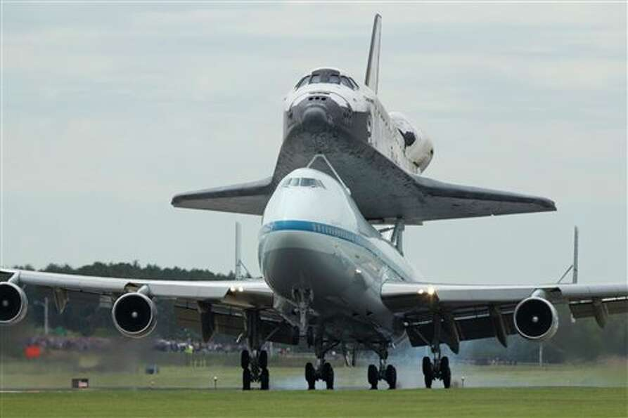 The space shuttle Discovery, sitting atop a 747 carrier aircraft, lands at Dulles International Airp