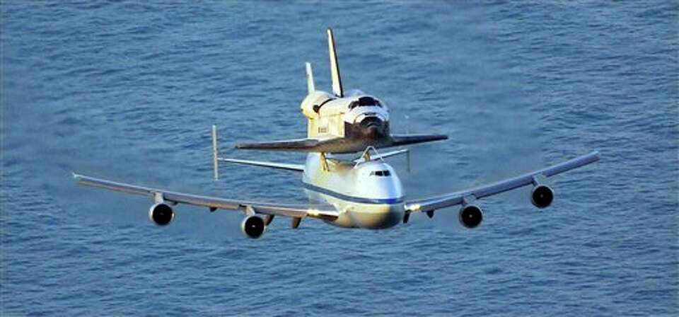 The Space shuttle Discovery, mounted on top of a modified 747, flies over the Atlantic Ocean as it m