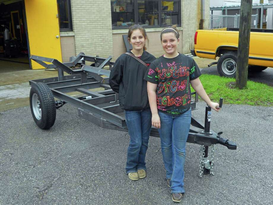 Shelby Armstrong (left) and Kiristen Vingoe stand before the trailer they built in the Bellaire High School Ag Mechanics class. Photo: Tom Behrens