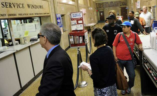 People wait in line at the Post Office on Middle Street in Bridgeport, Conn. Tuesday, April 17, 2012, tax day.  Tax payers have an extra two days to pay Uncle Sam since April 15 fell over the weekend. Photo: Autumn Driscoll / Connecticut Post