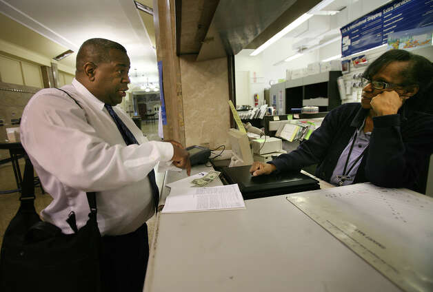 Gilbert Davis of Bridgeport picks up an extension form and a stamped envelope on the final day for tax filing at the Post Office on Middle Street in Bridgeport on Tuesday, April 17, 2012. Photo: Brian A. Pounds / Connecticut Post