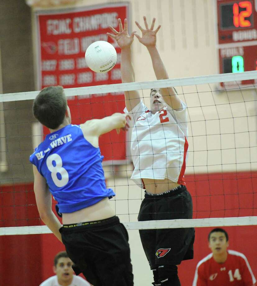 At left, Matt Collier # 8 of Darien High School gets his spike blocked by John Beneville # 2 of Greenwich during the boys high school volleyball match between Greenwich High School and Darien High School at Greenwich High School, Tuesday, April 17, 2012. Photo: Bob Luckey / Greenwich Time
