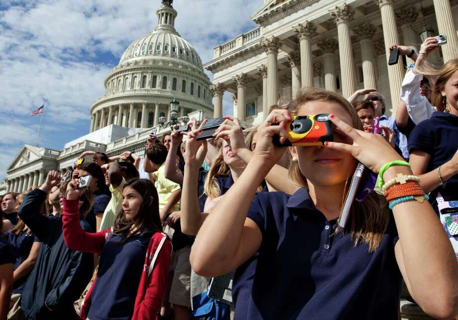 Sixth-graders visiting the Capitol from Macon, Ga., watch the final voyage of the space shuttle Discovery as it soars above Washington on Tuesday. Photo: J. Scott Applewhite / AP