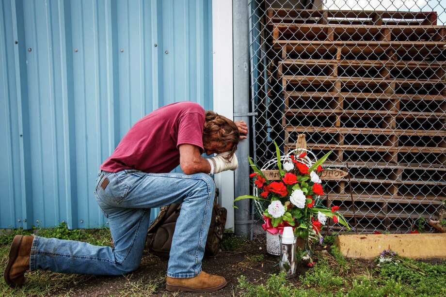 "Peter Welz bows his head as he kneels next to a memorial for his friend Miguel Ramos, 32, who died shortly after being gunned down on the night of April 4, in Houston, by four teenagers. ""He was a good man,"" Welz said. ""I keep telling people not to cry, he's in a better place now."" Photo: Michael Paulsen, Houston Chronicle / © 2012 Houston Chronicle"