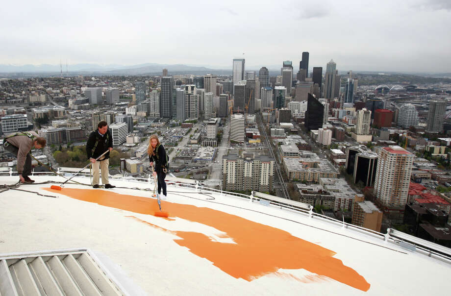 "From left, Stuart Rolfe, Jeff Wright and Mauren Wright, 15, Jeff's daughter, begin painting the roof of the Space Needle its original ""Galaxy Gold"" on Tuesday, April 17, 2012. Jeff Wright's father, Howard S. Wright, built the Space Needle. The icon is returning to its original color as part of the celebration of the 50th anniversary of the Needle and the Seattle Center. Photo: JOSHUA TRUJILLO / SEATTLEPI.COM"