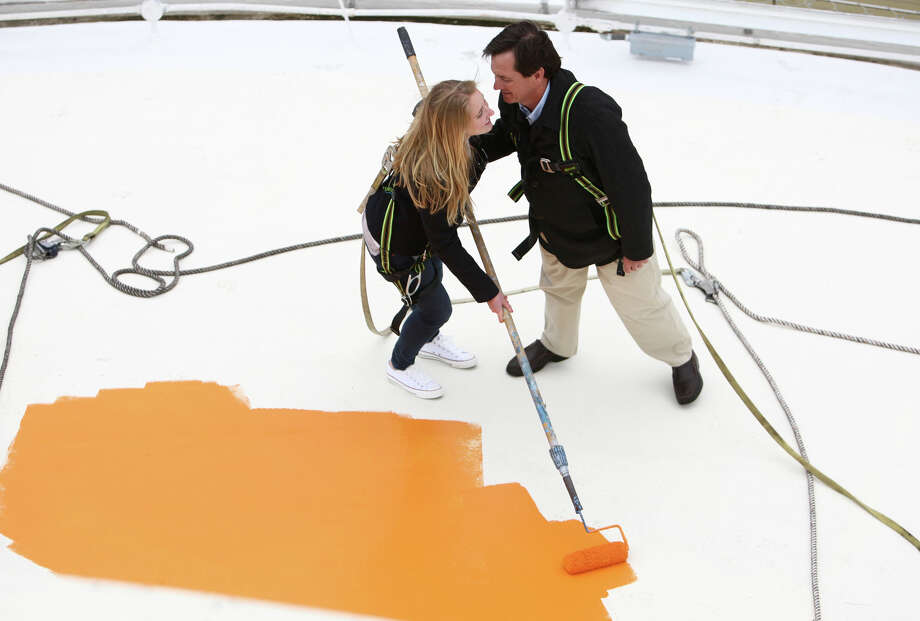 Jeff Wright gives his daughter Mauren, 15, a kiss as they begin painting the roof of the Space Needle its original 'Galaxy Gold' on Tuesday, April 17, 2012. Jeff said being up there with his daughter reminded him of the time he spent on the iconic structure with his own dad, Howard S. Wright. Photo: JOSHUA TRUJILLO / SEATTLEPI.COM