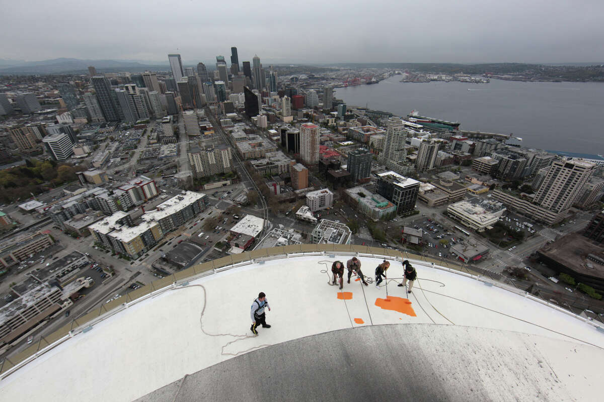 Dave Hughbanks, Stuart Rolfe, Mauren Wright, 15, and her dad Jeff Wright begin painting the roof of the Space Needle its original