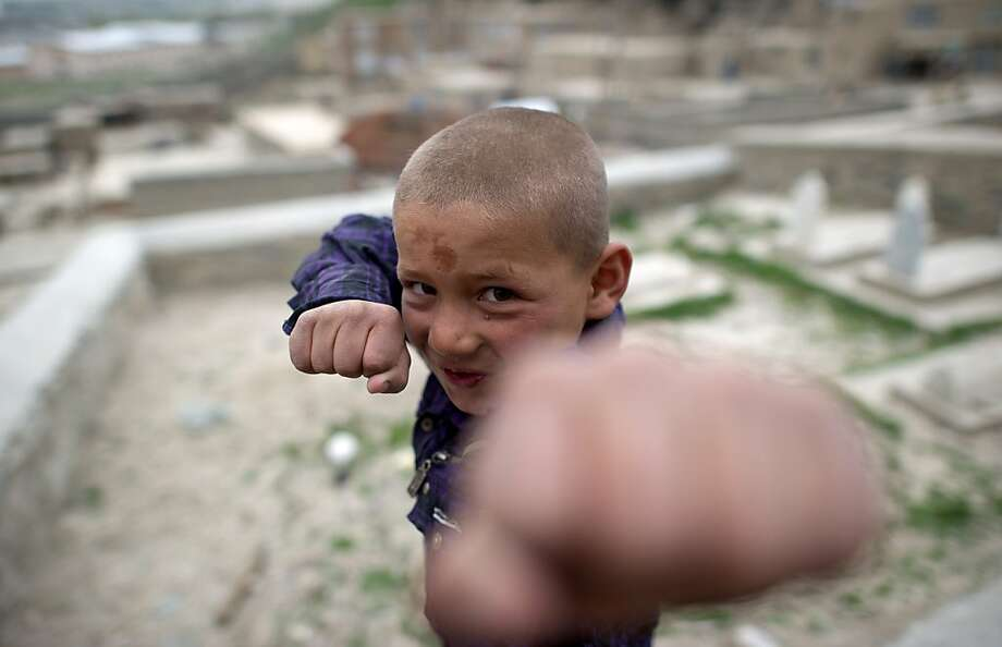 TOPSHOTS An Afghan boy pretends to box at a graveyard in the city of Kabul on April 17, 2012.  Poverty and an ongoing insurgency by the ousted Taliban still pose a threat to the stability of the country.  AFP PHOTO/ JOHANNES EISELE (Photo credit should read JOHANNES EISELE/AFP/Getty Images) Photo: Johannes Eisele, AFP/Getty Images
