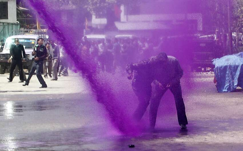 Police use colored water from a water cannon to disperse protesting Kashmiri government employees during a protest against the government in Srinagar, India, Tuesday, April 17, 2012. The employees demanded payment of arrears in salaries and raising of retirement age among other demands. (AP Photo/Mukhtar Khan)