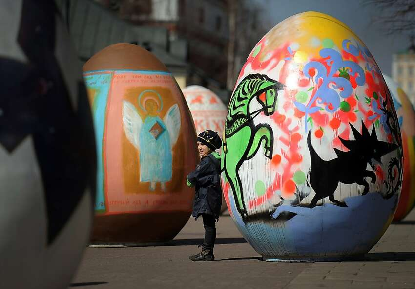 TOPSHOTS A girl walks through a giant eggs installation in central Moscow on April 17, 2012 during the Easter Eggs Festival. AFP PHOTO/ ANDREI SMIRNOV (Photo credit should read ANDREY SMIRNOV/AFP/Getty Images)