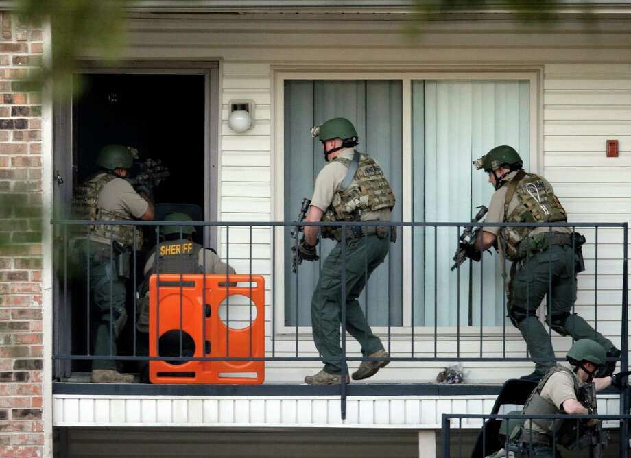 Law enforcement officers enter an apartment near the scene where a mother was killed and her baby kidnapped Tuesday, April 17, 2012, in Spring. A newborn boy was abducted from his screaming mother after she was repeatedly shot outside a suburban Houston pediatric center on Tuesday, according to investigators searching for the suspected shooter who sped off with the infant in a blood-stained Lexus. Photo: David J. Phillip, Associated Press
