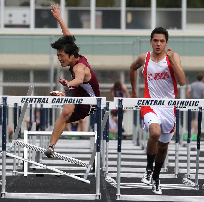 St. Anthony's Hoon Seol (left) falls after hitting a hurdle near Brownsville St. Joseph's Andres Cardenas in the 110-meter hurdles during the TAPPS 5A South Regional track meet held Monday April 16, 2012 at Central Catholic High School. Cardenas finished first.