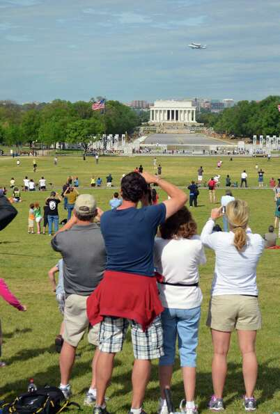 Visitors to the National Mall snapped pictures of Discovery as it flew over the Lincoln Memorial in