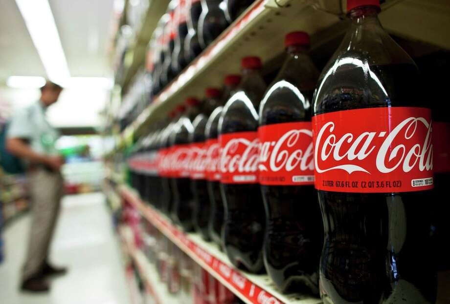 A customer shops near bottles of Coca-Cola Co. drinks at a supermarket in Brooklyn. Coca-Cola said Tuesday that sales increased around the world. Photo: Ramin Talaie / © 2011 Bloomberg Finance LP