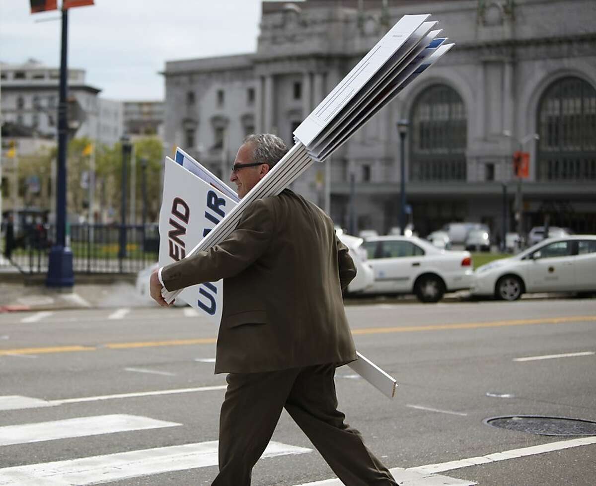 A businessman collects signs as he leaves the rally at City Hall, in San Francisco, California on Tuesday, April 17, 2012.