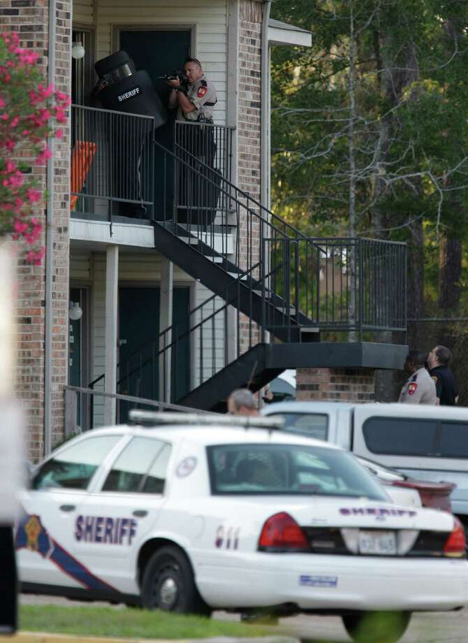 Police surround an apartment at the Fawn Ridge Apartments in The Woodlands. A car matching the description of one involved in an earlier kidnapping and shooting was seen at the apartment complex. Photo: Melissa Phillip, Houston Chronicle / © 2012 Houston Chronicle