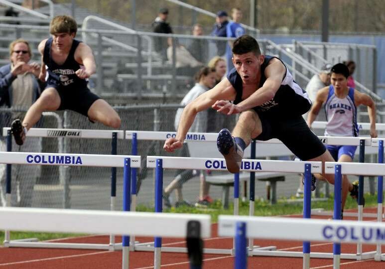 Columbia's Jake Alviene, right, flys to a victory in the 110 hurdles during a high school track meet