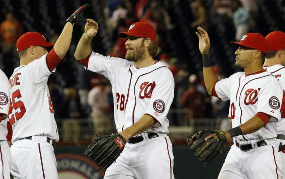 Washington Nationals' Adam LaRoche, left, celebrates with Jayson Werth (28) and Ian Desmond, right, after beating the Houston Astros. (Ann Heisenfelt / Associated Press)