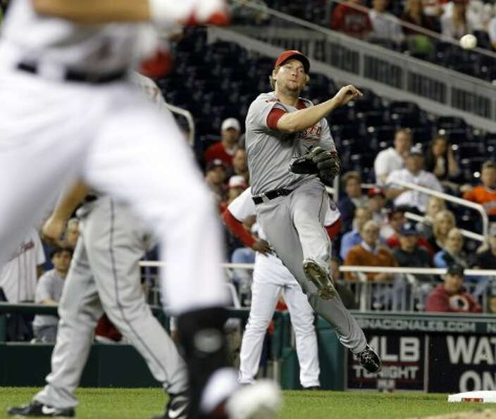 Houston Astros third baseman Chris Johnson, right, throws out Washington Nationals' Mark DeRosa afte