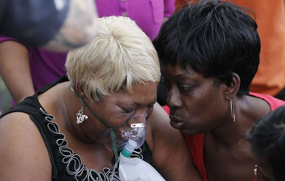 Debra Forrest, right, consoles a family member of victims of a fatal fire, Tuesday, April 17, 2012, in Philadelphia.  Fire tore through a row house early Monday, killing two young children and two adults in the city's third fatal blaze in a week. (AP Photo/Matt Rourke) Photo: Matt Rourke, Associated Press