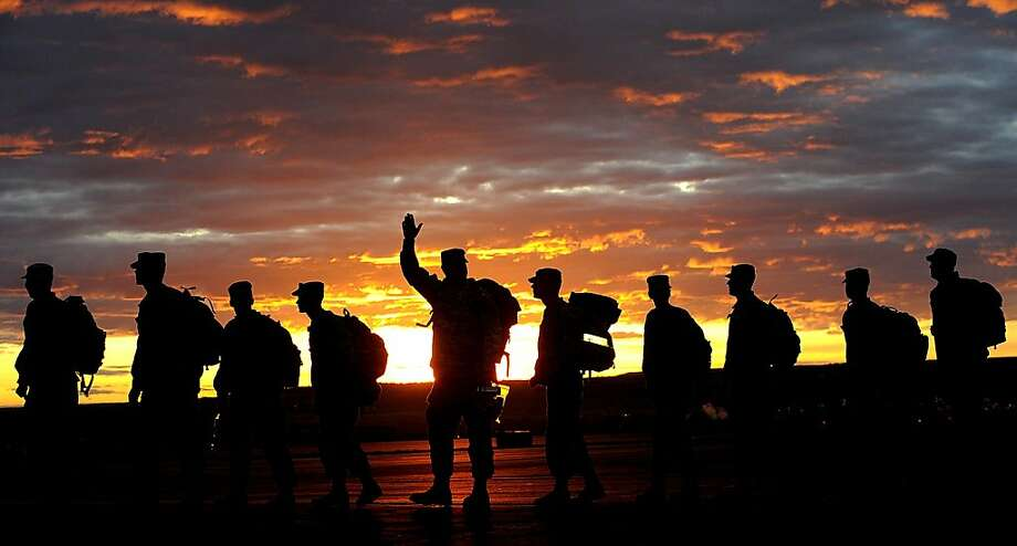 A soldier waves backto his family as the Montana Army National Guard 484th MP Company departs from Edwards Jet Center in Billings, Mont. The unit is headed to Afghanistan.  Photo: Larry Mayer, Associated Press