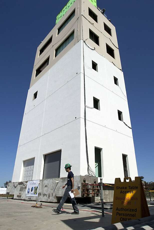 A researcher walks in front of a five-story building constructed to study earthquakes at a facility run by the University of California at San Diego Tuesday, April 17, 2012, in San Diego. To study the affects of earthquakes, researchers will repeatedly shake a building over a span of two weeks as part of the $5 million experiment funded by government agencies, foundations and others. (AP Photo/Gregory Bull) Photo: Gregory Bull, Associated Press