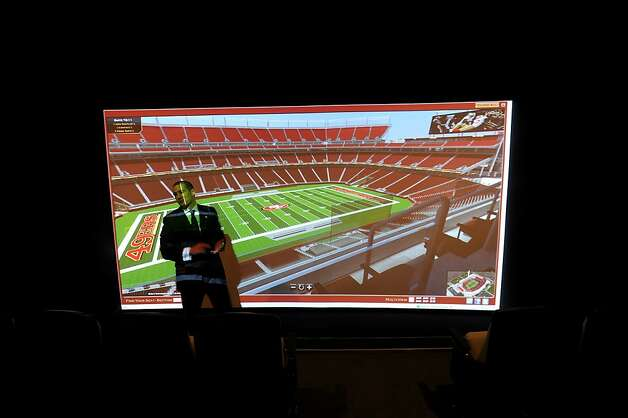 Al Guido, vice president for new stadium sales and service with the 49ers, gives a tour of the team's New Stadium Preview Center in Santa Clara, Calif., on Tuesday, Sept. 27, 2011. The screen at right replicates the view from different areas of the stadium so ticket holders can evaluate seat choices. Photo: Noah Berger, Special To The Chronicle