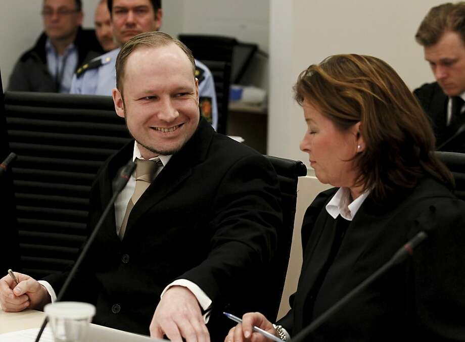 Accused Norwegian Anders Behring Breivik smiles at his defence lawyer Vibeke Hein Baera at the courtroom, in Oslo, Norway, Tuesday April 17, 2012. The anti-Muslim fanatic who admitted to killing 77 people in a bomb-and-shooting massacre is set to take the stand in his terror trial. Anders Behring Breivik will have five days to explain why he set off a bomb in Oslo's government district, killing eight, and then gunned down 69 at a Labor Party youth camp outside the Norwegian capital. (AP Photo/Heiko Junge/Scanpix Norway/POOL) Photo: Heiko Junge, Associated Press