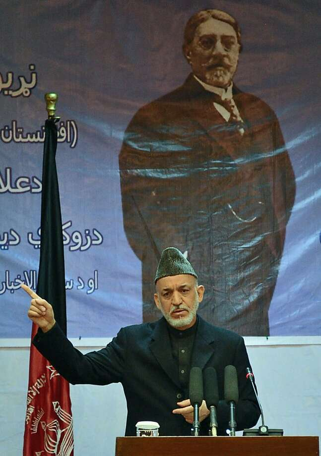 Afghan President Hamid Karzai (C) gestures as he delivers a speech to mark the 150th anniversary of the father of Afghanistan journalism, Mahmood Tarzi (background picture), in Kabul on April 17, 2012.    Australia said that it will bring its troops home from Afghanistan a year earlier than planned with most soldiers withdrawn in 2013 after significant security gains over the past 18 months. Australian Prime Minister Julia Gillard said they would begin leaving as soon as Afghan President Hamid Karzai declared Afghans would take responsibility for Uruzgan province, where most Australian forces are based. Photo: Bay Ismoyo, AFP/Getty Images
