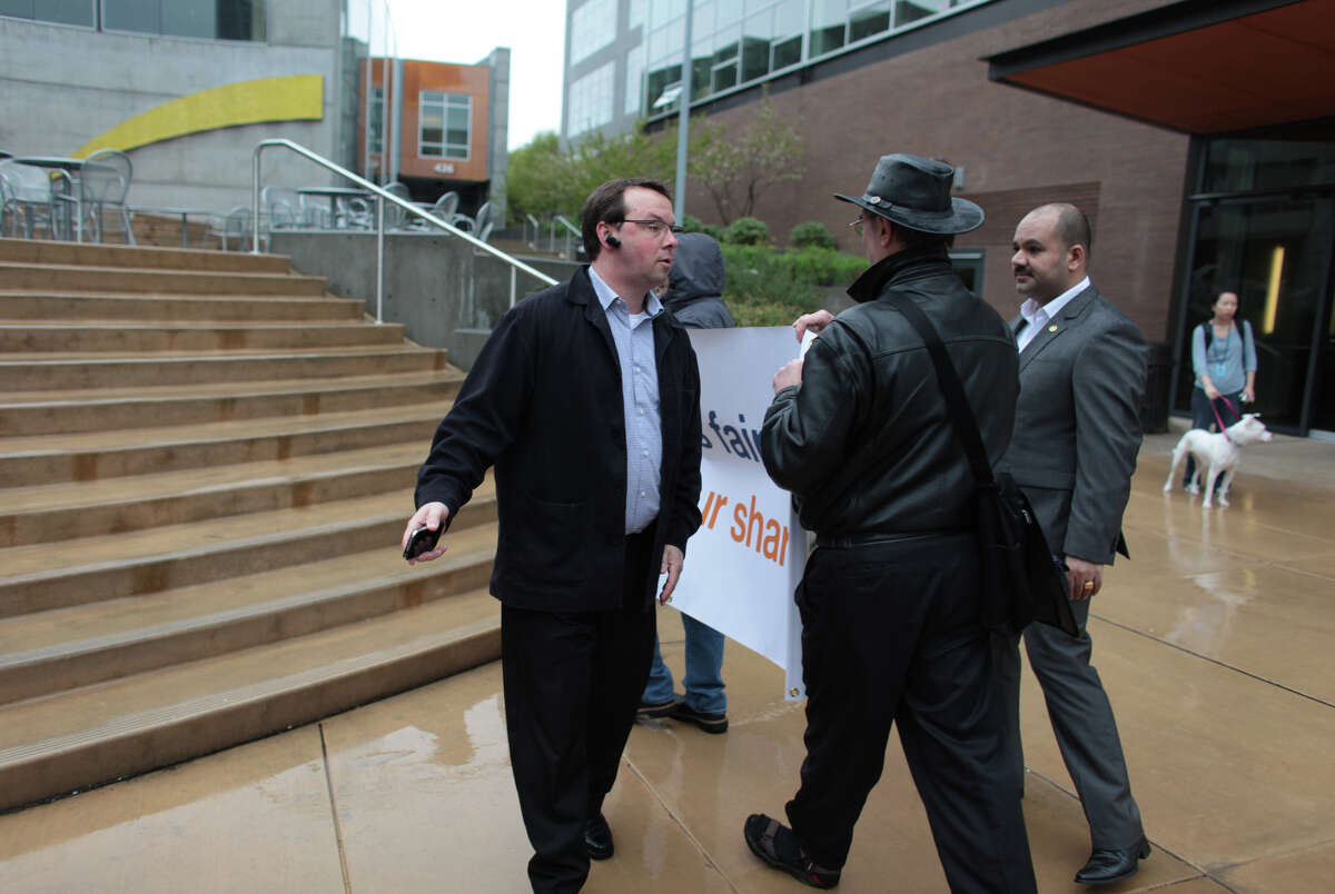 Security guards try to prevent protesters from walking onto the Amazon campus during a tax day protest at Amazon's South Lake Union corporate campus on Tuesday, April 17, 2012. The protesters were calling attention to what they said is an unfair tax rate paid by the Seattle-based corporation.