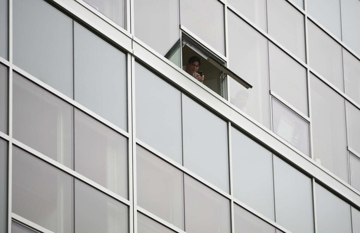 A person in one of the Amazon buildings looks out at protesters during a tax day protest at Amazon's South Lake Union corporate campus on Tuesday, April 17, 2012. The protesters were calling attention to what they said is an unfair tax rate paid by the Seattle-based corporation.