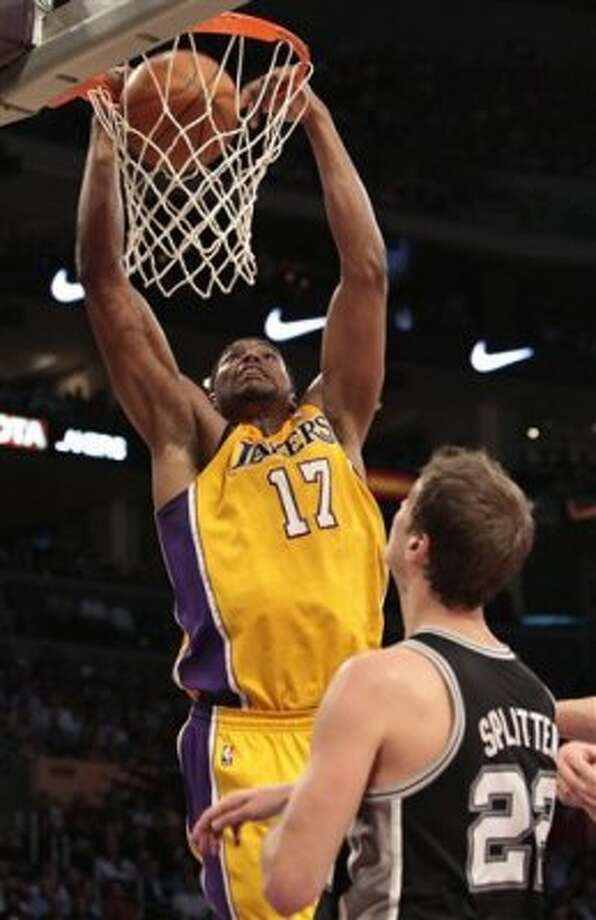 Los Angeles Lakers center Andrew Bynum (17) dunks as San Antonio Spurs' Tiago Splitter (22) looks on during the first half of their NBA basketball game, Tuesday, April 17, 2012, in Los Angeles. (AP Photo/Jason Redmond) (AP)