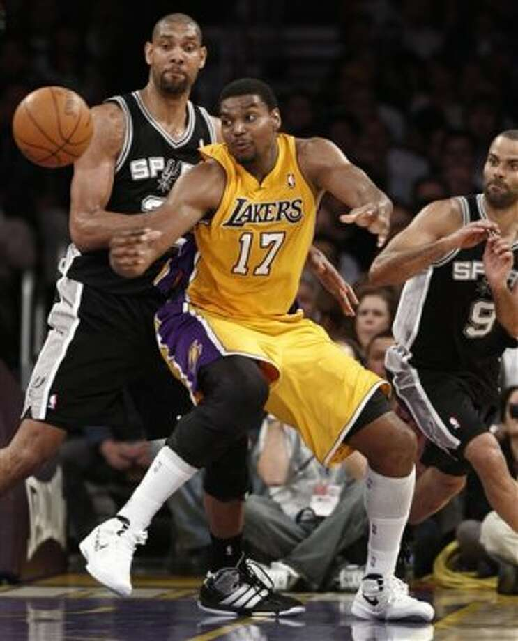 Los Angeles Lakers center Andrew Bynum (17) watches the ball as San Antonio Spurs' Tim Duncan, left, and Tony Parker (9) defend during the second half of their NBA basketball game, Tuesday, April 17, 2012, in Los Angeles. The Spurs won 112-91. (AP Photo/Jason Redmond) (AP)