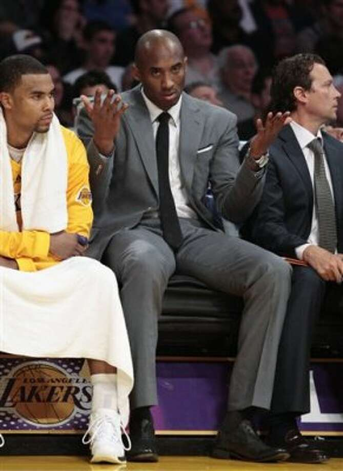 Los Angeles Lakers' Kobe Bryant, center, reacts as Ramon Sessions, left, looks on from the bench as the San Antonio Spurs score during the second half of their NBA basketball game, Tuesday, April 17, 2012, in Los Angeles. The Spurs won 112-91. (AP Photo/Jason Redmond) (AP)