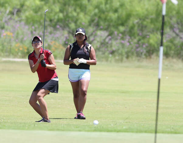 Southside's Iisha Tarin (left) reacts to her her chip shot as the ball drifts toward the No. 9 hole at the Region IV-4A girls golf tournament at the Golf Club of Texas on Tuesday, Apr. 17, 2012. Kin Man Hui/Express-News. Photo: Kin Man Hui, Express-News / ©2012 San Antonio Express-News