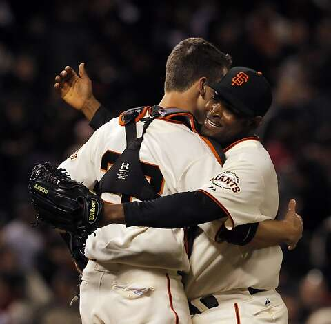 Santiago Casilla gets a hug from Buster Posey after Casilla notched a save against the Phillies, the Giants first save since closer Brian Wilson was put on the disabled list. The San Francisco Giants played the Philadelphia Phillies at AT&T Park in San Francisco, Calif., on Tuesday, April 17, 2012, and defeated the Phillies 4-2. Photo: Carlos Avila Gonzalez, The Chronicle