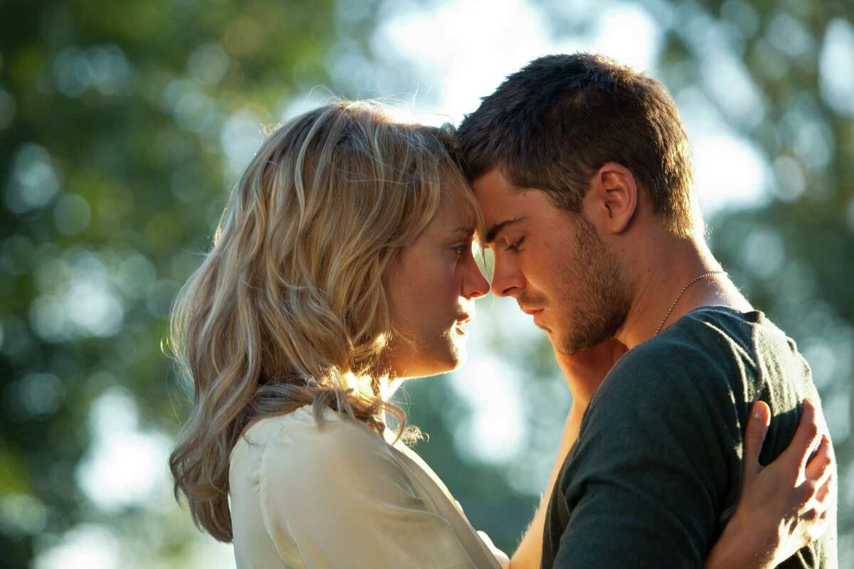 In this film image released by Warner Bros, Taylor Schilling, left, and Zac Efron are shown in a scene from