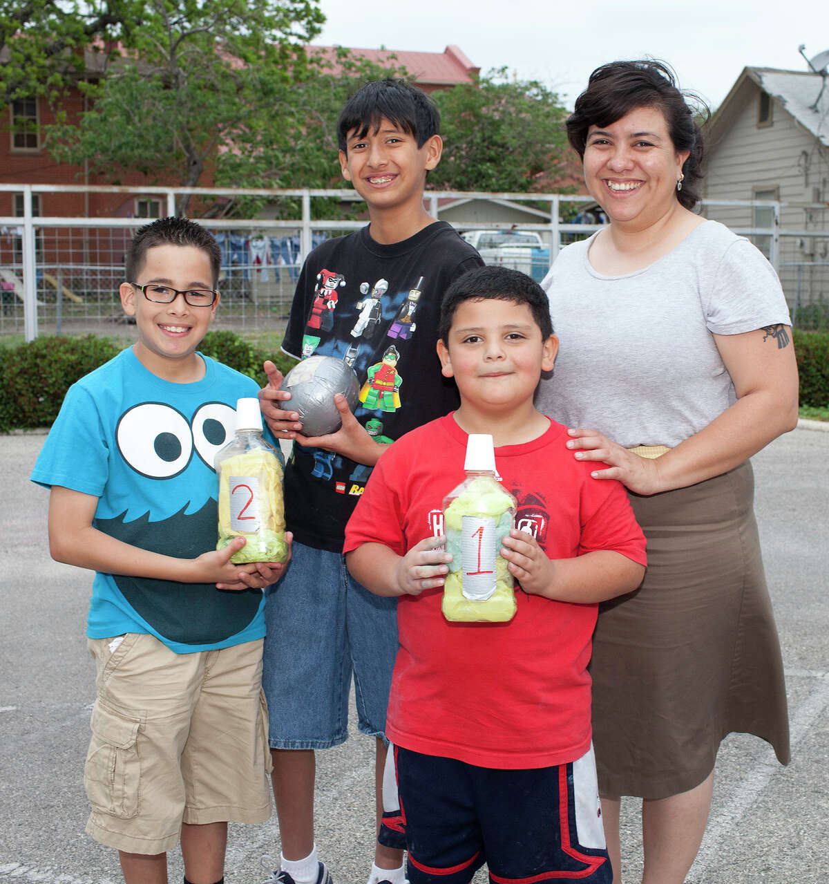 Christopher Freiry, 11 (from left), and Nicholas Cortinas, 10, get together with Daniel Ramirez, 6, and instructor Jessica O. Guerrero during the Guadalupe Cultural Arts Center's family block party at the center.