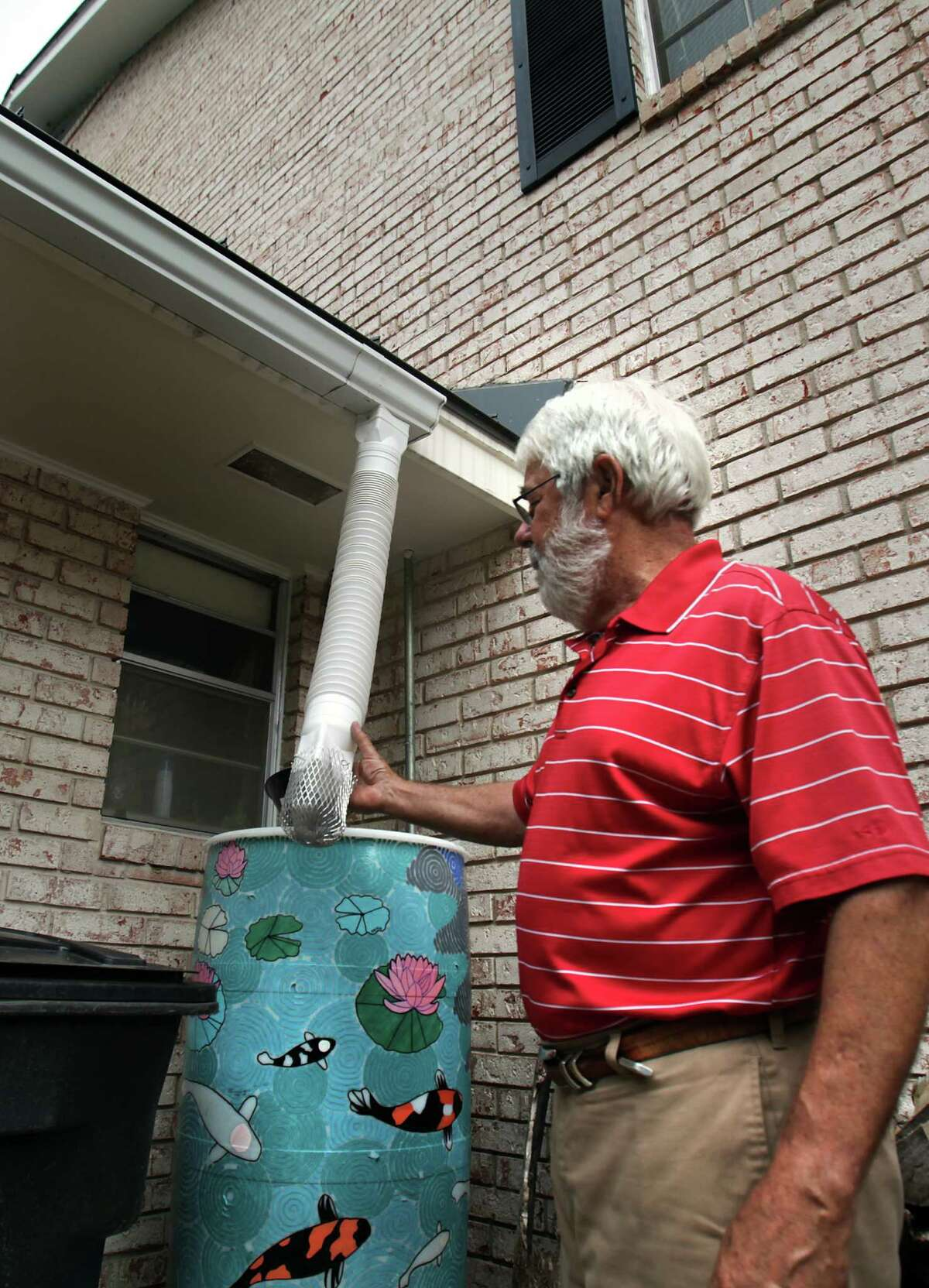 Steve Hixon checks the downspout on his water collection system at his San Antonio home. Wednesday, April 11, 2012.