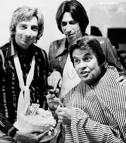 Television's Dick Clark helps cut his 47th birthday cake during a break in rehearsals for an upcoming television special in Santa Monica, Ca., December 1, 1976. Helping him celebrate are (l) singer Barry Manilow and comedian David Brenner. Clark is wearing a smock to protect him while he is madeup. Photo: Anonymous, AP / 1976 AP