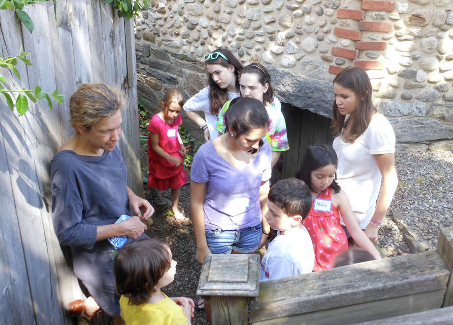Elizabeth DeVoll, left, leader of the Westport Historical Society's school vacation camp, tells children about the root cellar of the cobblestone barn on the group's property. Photo: Mike Lauterborn / Westport News contributed
