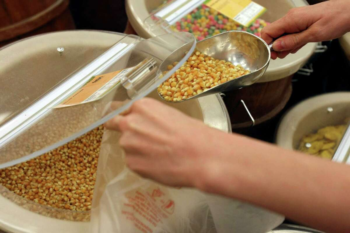 TASTE: Christina Isenhower (CQ) scoops popcorn kernels into a bag while shopping in the bulk foods section at Sprouts on Tuesday April 17, 2012. Helen L. Montoya/San Antonio Express-News