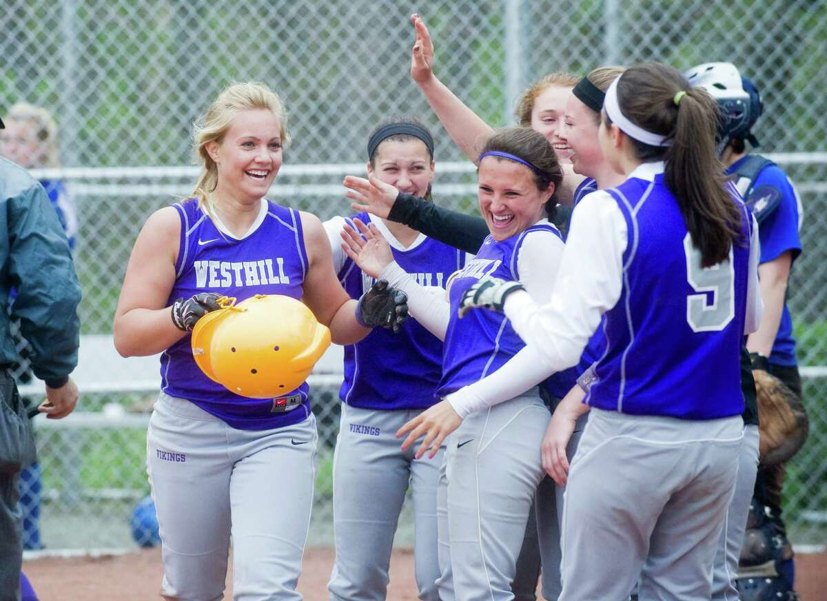 Westhill greets Allison Macari after she brought in a homer as Westhill High School hosts Ludlowe in a softball game in Stamford, Conn., April 18, 2012.